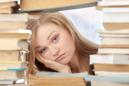 Young woman sitting behind books - tired photo
