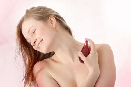 Sensual blond woman applying perfume on her body photo