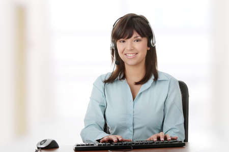 Young beautiful customer service operator girl in headset ,sitting at the desk photo