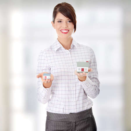 Young businesswoman holding two house models photo
