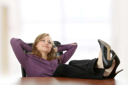 feet relaxing: Young beautiful business lady having a rest at the working place.