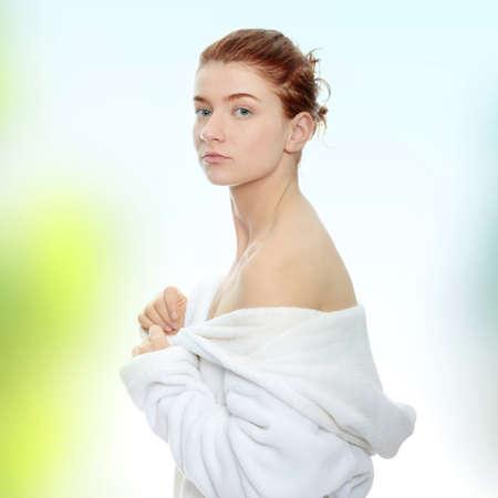 Young beautiful redhead woman wearing bathrobe photo