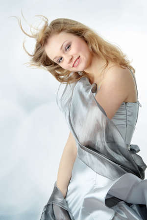 Young beautiful blond woman in elegant, evening, silver dress dancing with wind (hair blowing) photo