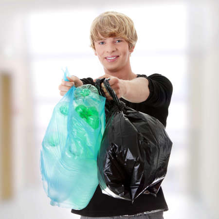Young man carrying a plastic trash bags full with empty recyclable household material. photo