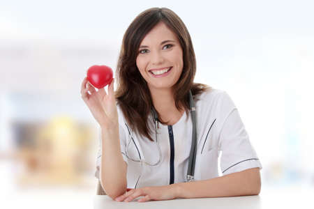 Young female doctor with heart in her hand.  photo