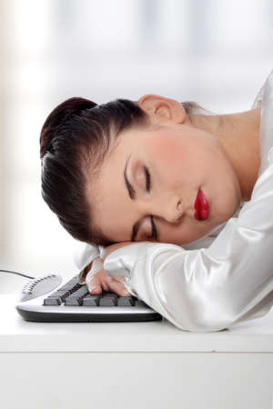 Young businesswoman sleeping on the keyboard in the office.  photo