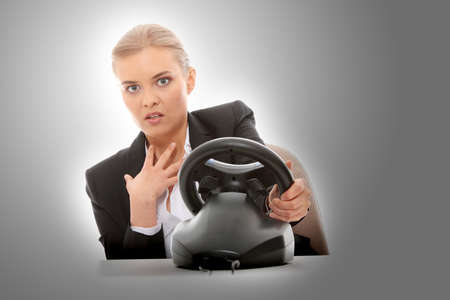 Young caucasian business woman playing on computer (with steering wheel) photo