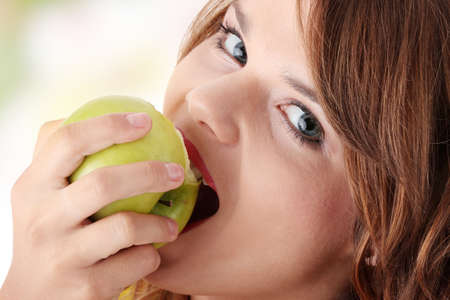 Teen girl eating grean apple isolated on white background photo