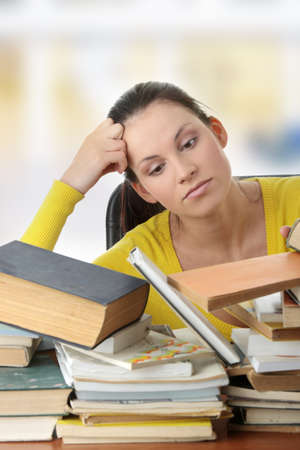 Young woman sitting behind books   photo