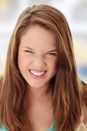 Close Up Shot of a Beautiful Angry Teenager, isolated on white background  photo