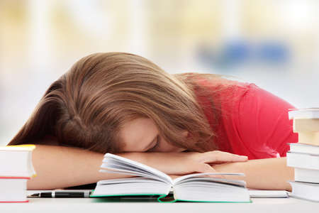 bored student: Teenage girl studying at the desk being tired, isolated on white  Stock Photo