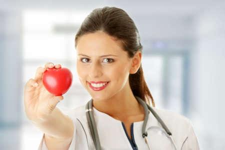 Giovane infermiera con il cuore in mano, isolato su sfondo bianco  Archivio Fotografico - 9024342