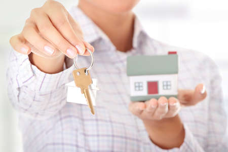 doorkey: Young businesswoman  (real estate agent) with hose model and keys