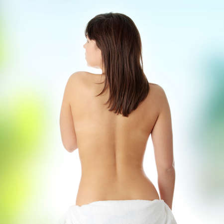 woman nude standing: Young beautiful woman topless, in towel, view from back Stock Photo
