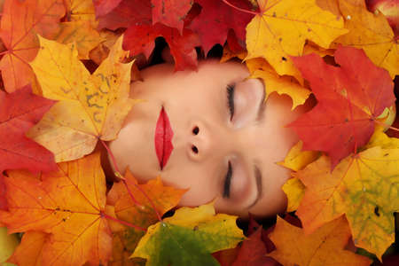 autumn young: Close-up of a woman face in autumn leafs