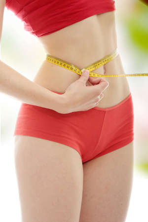 red panties: Beautiful young caucasian woman measuring her body with tape