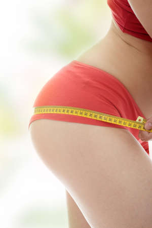 Beautiful young caucasian woman measuring her body with tape photo