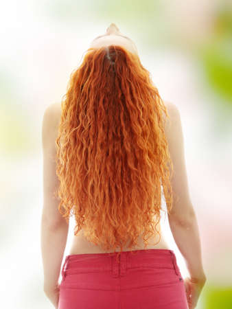 Rear view of the young female with beauty curly long hairs photo