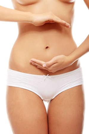 dolor de estomago: Bello cuerpo femenino aislados en blanco. Sexy mujer joven en bragas blancas  Foto de archivo