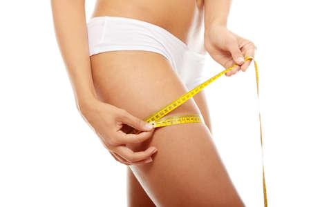 cintas metricas: Closeup foto de piernas de una mujer de raza blanca. Ella es medir su muslo con una medida de cinta m�trica de amarilla despu�s de una dieta