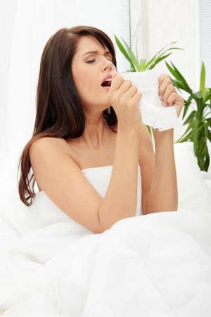 mujer pensativa: Mujer enferma sentado en la cama con tejido y soplando su nariz en ella