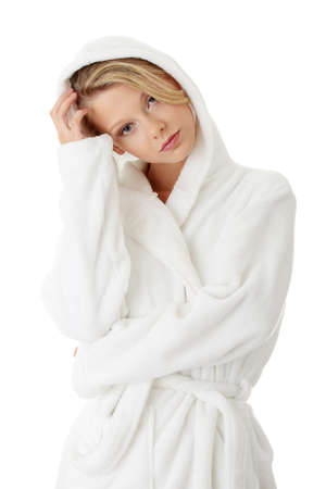 Young beautiful blond teen woman in bathrobe, isolated on white photo