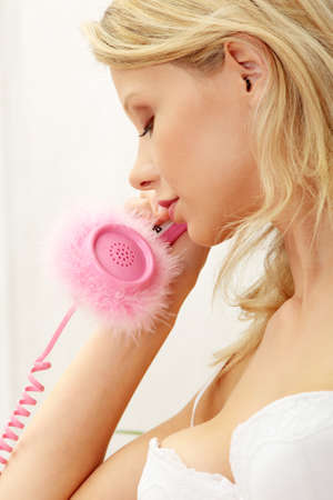 Beautiful young woman in underwear talking by pink phone photo