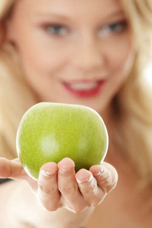 Young blond woman with green apple on her hand - healthy eating concept photo
