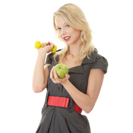 Young blond woman with green apple and yellow dumbbell - healthy living concept  photo