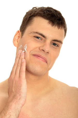 Happy man after shaving applying moisturizing cream upon his face  photo