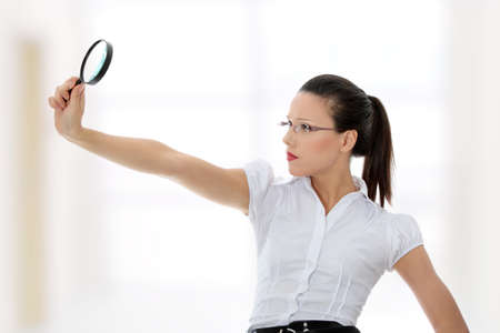 enlargement: Young attractive business woman looking into a magnifying glass