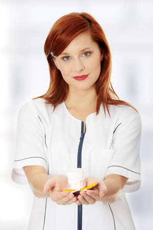 Female doctor with hand full of pills photo