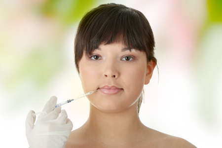 Woman getting botox injection, looking relaxed   photo
