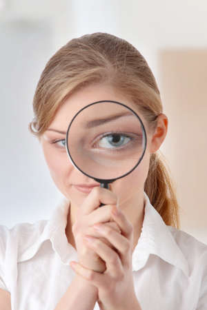 The woman with a magnifier in a hand  photo