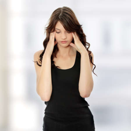 Woman with headache holding her hand to the head photo