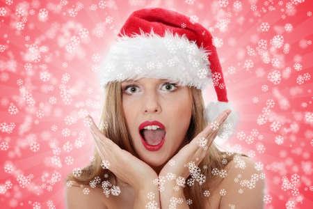 Surprised christmas woman wearing a santa hat smiling  photo