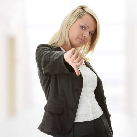 Attractive blonde woman in professional business suit pointing her thumbs down Stock Photo - 9033321