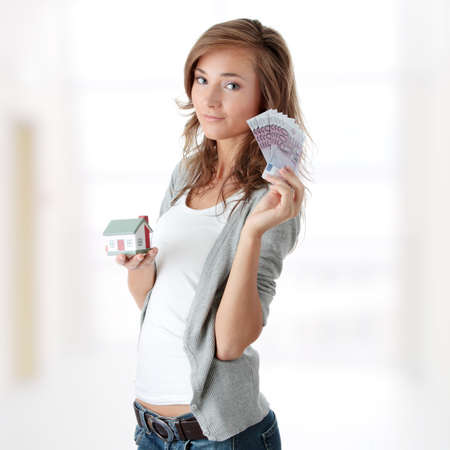 Beautiful young woman holding euros bills and house model Stock Photo - 9031051