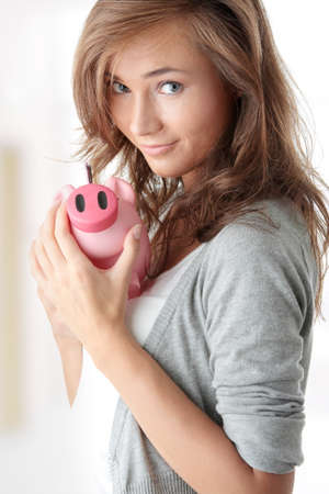 Young beautiful woman standing with piggy bank (money box) Stock Photo - 9033580