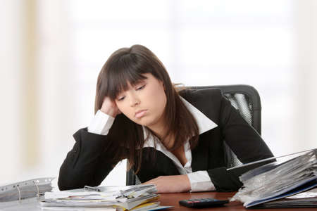 refund: Exhausted female filling out tax forms while sitting at her desk.  Stock Photo