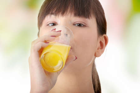 Young beautiful fit caucasian woman drinking orange juice from glass photo