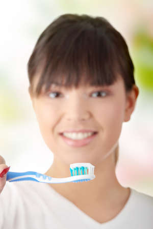 Young beautiful woman washing her teeth with blue brush - focus on brush photo