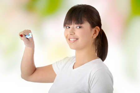 Young beautiful woman washing her teeth with blue brush photo