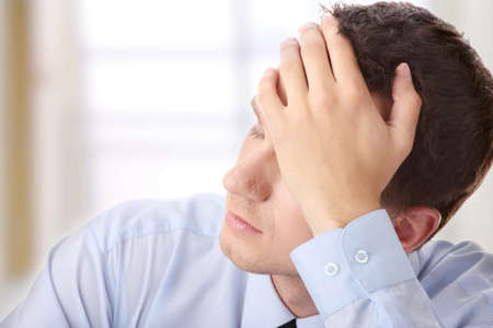 Businessman in depression with hand on forehead photo