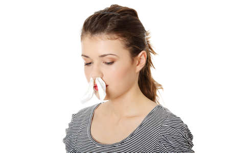 Teen woman with tissue in her nose, isolated on white background  photo