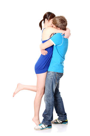 Beautiful young couple kissing against white background  Stock Photo - 9033319