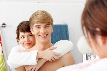 Young couple at bathroom. Isolated on white. photo