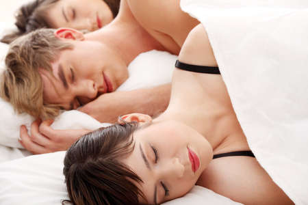Young handsome man lying in bed with two girls  photo