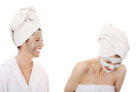 Young happy women with facial clay mask , isolated on white photo