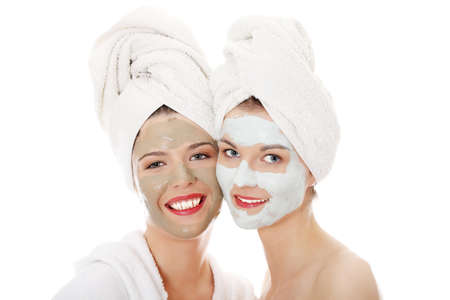 body mask: Happy two young woman with anti-aging masks . Isolated on white background. Stock Photo
